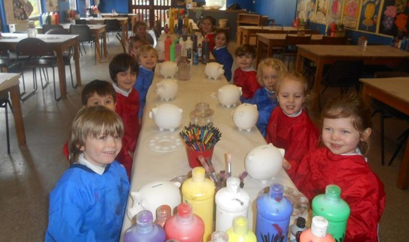 Children decorating piggy banks